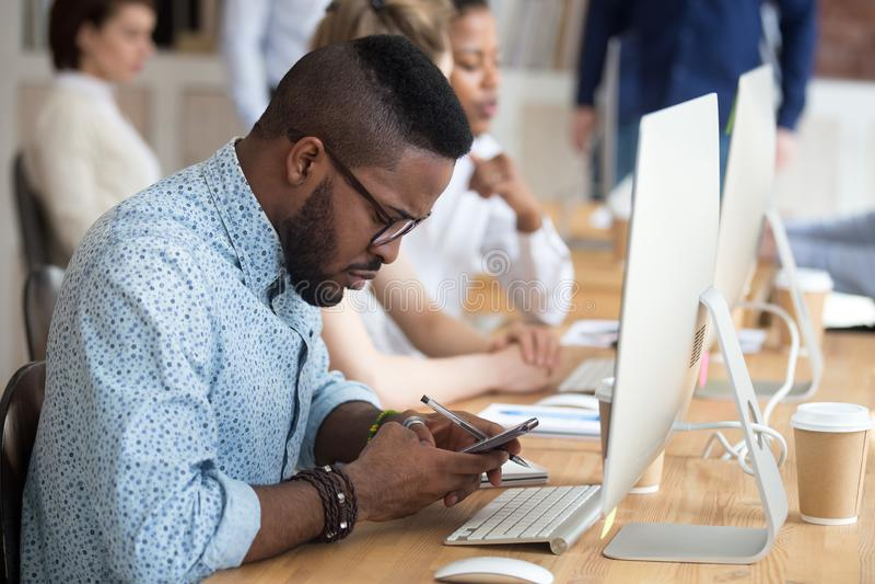 Allvarlig afrikansk amerikanman som använder smartphonen på arbetsplatsen fotografering för bildbyråer