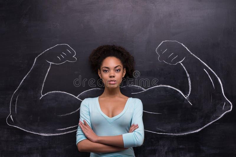 Allvarlig afro--amerikan kvinna med målat muskulöst fotografering för bildbyråer