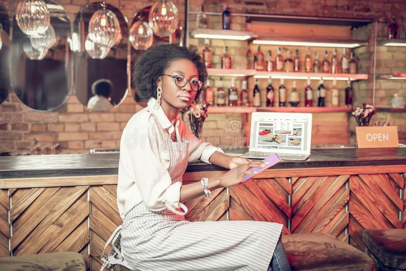 Allvarlig Afro--amerikan lockig-haired stångarbetare som klickar på minnestavlan arkivfoto
