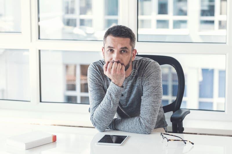 Allvarlig anställd arbetar i ljust och hemtrevligt kontor arkivbilder