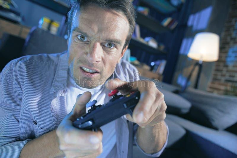 Allvarlig beslutsam man som spelar en videospel arkivbilder