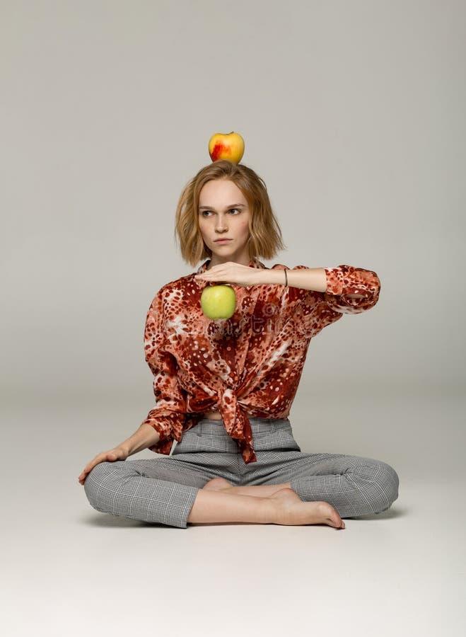 Allvarlig blond flicka i den moderiktiga röda skjortan som sitter i yogaposition arkivbilder