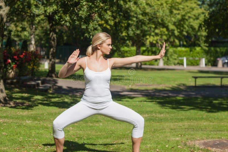 Allvarlig blond kvinna som gör yoga arkivfoton