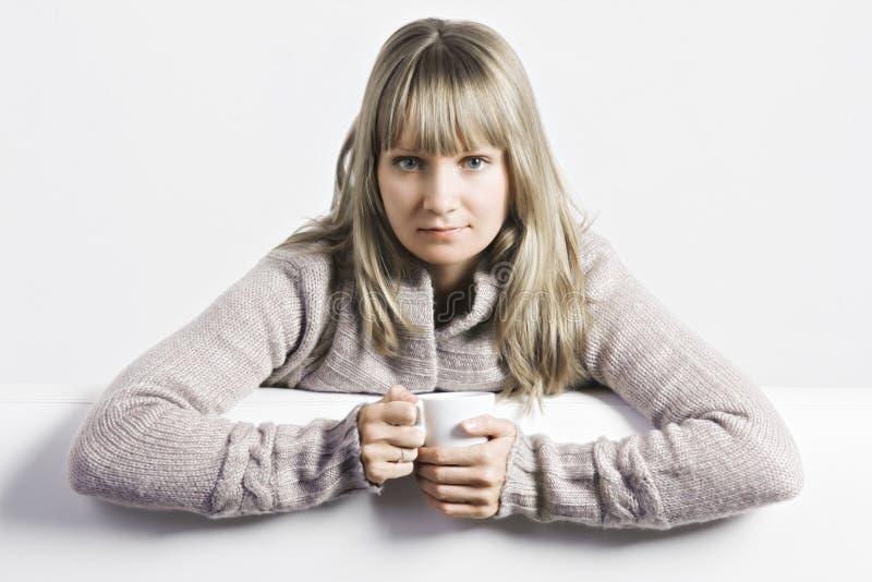 Allvarlig blondin med den vita koppen fotografering för bildbyråer