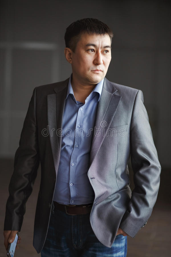 Allvarlig brutal asiatisk affärsman med telefonen in royaltyfri foto