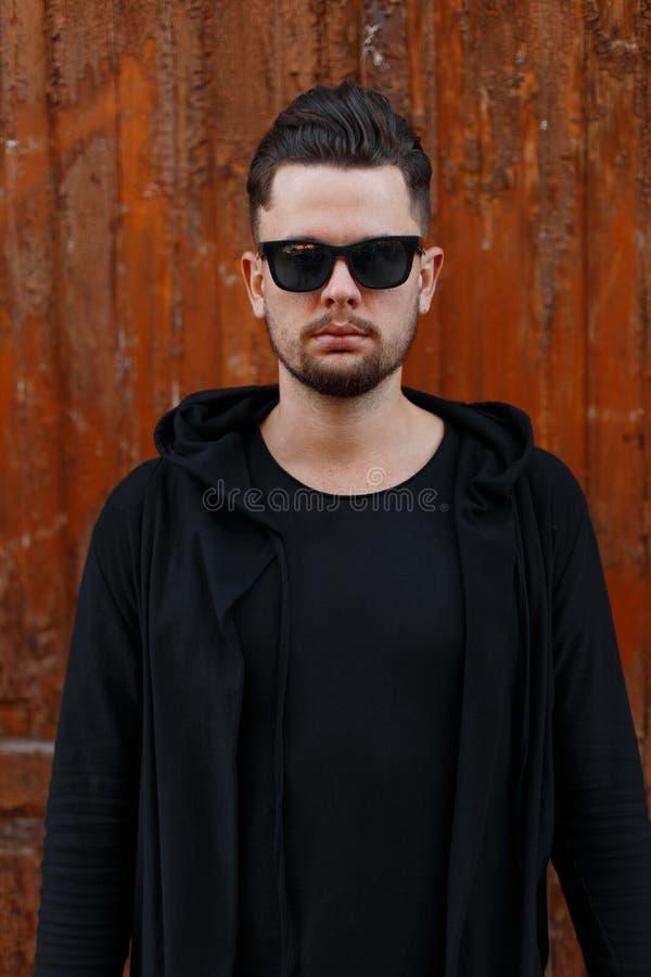 Allvarlig brutal stilig ung manlig hipster med den trendiga frisyren med skägget i stilfull solglasögon i modern svart kläder royaltyfri fotografi