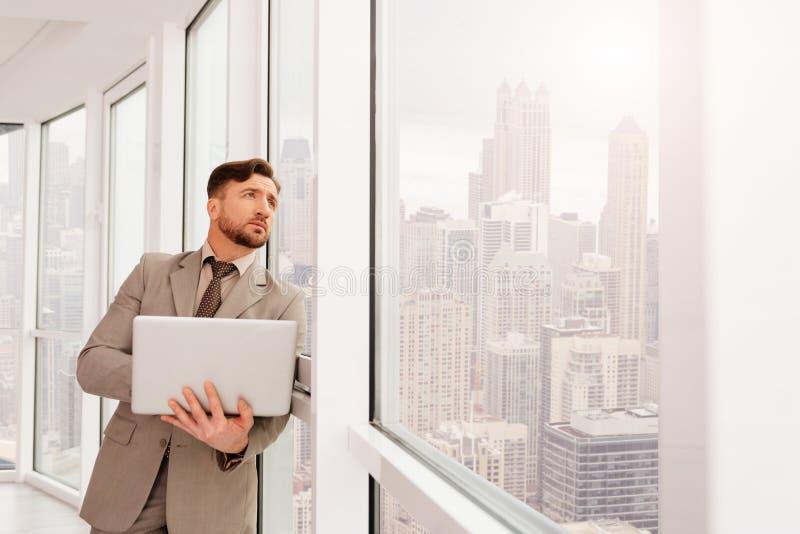 Allvarlig businesssmanbenägenhet på kontorsfönstret royaltyfri fotografi