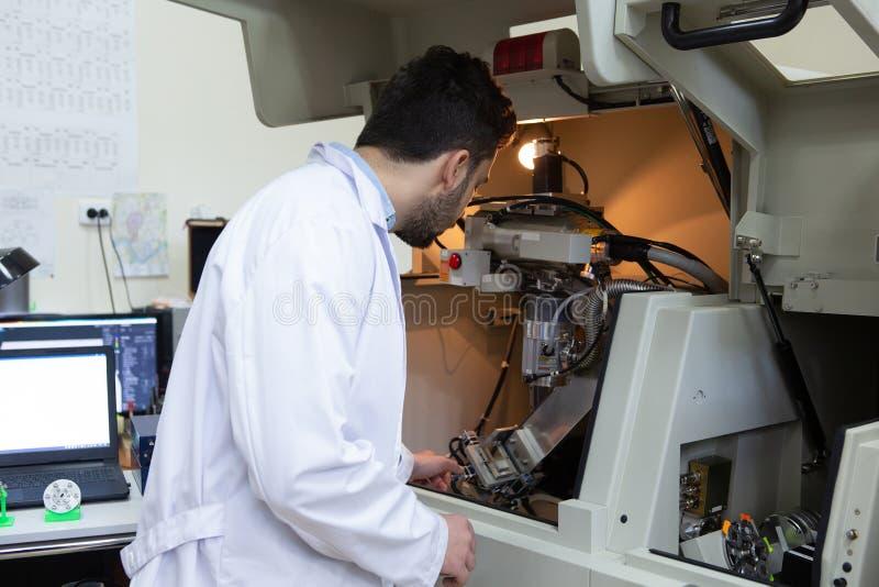 Allvarlig clinician som studerar den kemiska beståndsdelen i arbetsmiljö arkivfoto