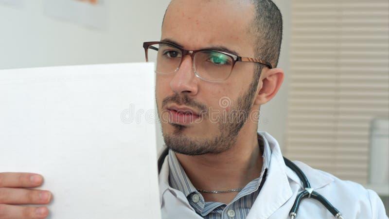 Allvarlig doktor som kontrollerar viktig medicinsk analys royaltyfri foto