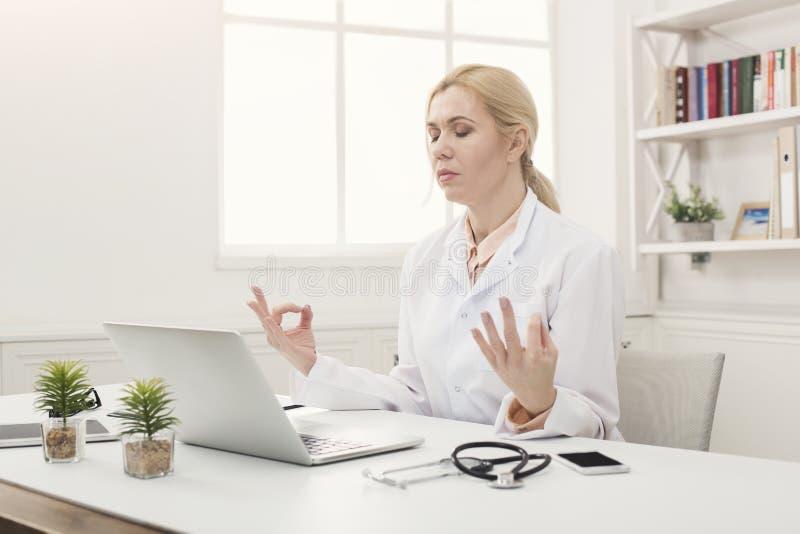 Allvarlig doktor som kopplar av i hennes kontor royaltyfri fotografi