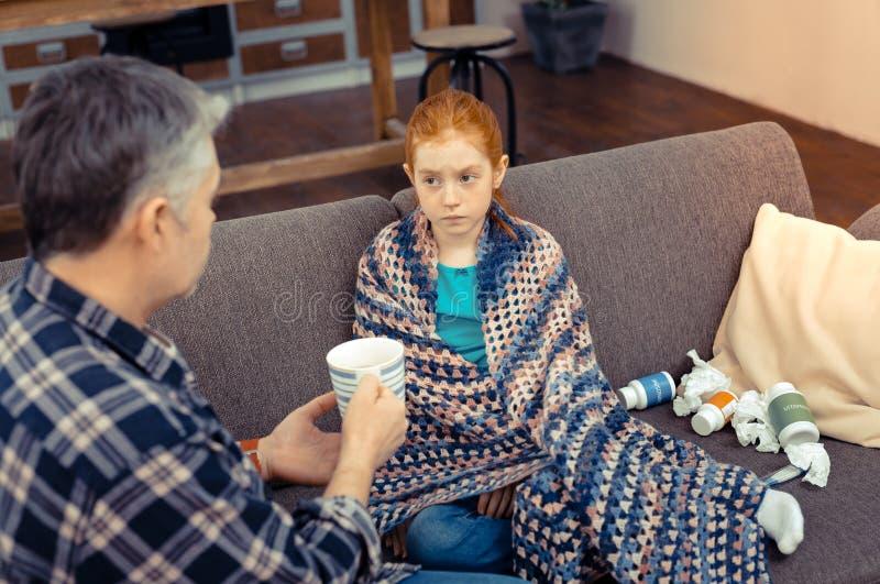 Allvarlig dyster flicka som ser hennes fader fotografering för bildbyråer
