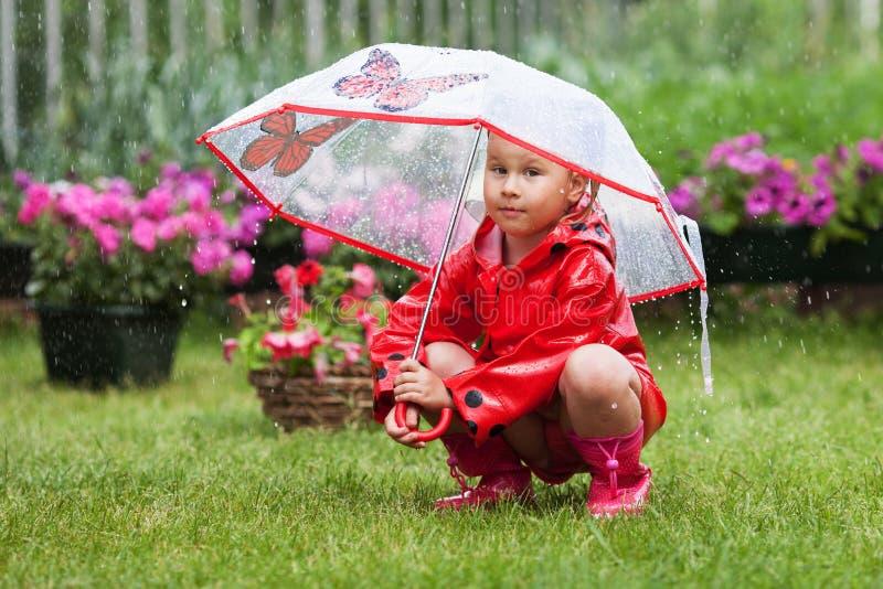 Allvarlig eftertänksam nätt liten flicka i röd regnrock med paraplyet fotografering för bildbyråer