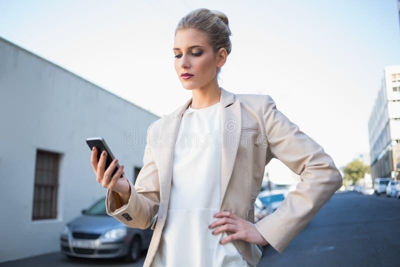 Allvarlig elegant affärskvinna som ser hennes smartphone royaltyfria foton