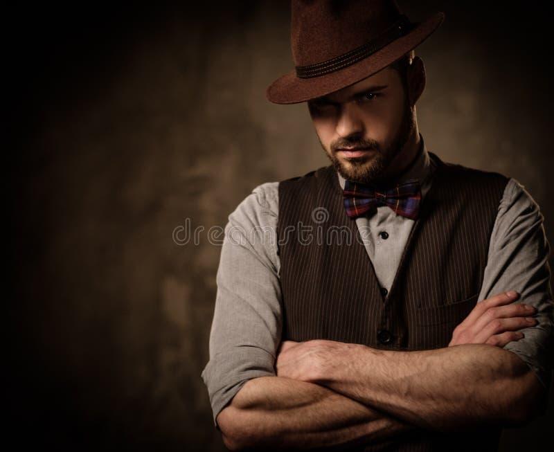 Allvarlig gammalmodig man med hatten som poserar på mörk bakgrund arkivfoto