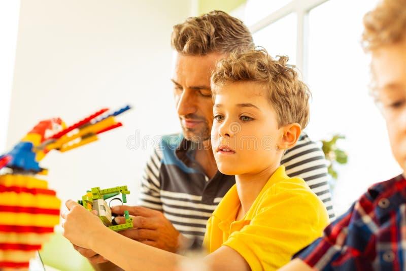Allvarlig gullig pojke som fokuserar på leksakerkonstruktion royaltyfria bilder