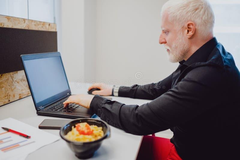 Allvarlig hög man som arbetar på en bärbar dator i kontoret arkivbild