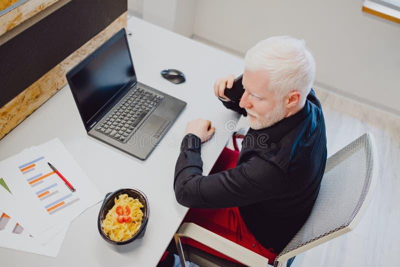 Allvarlig hög man som talar på telefonen i kontoret royaltyfri fotografi