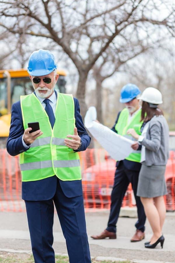 Allvarlig hög tekniker eller affärsman som använder hans smarta telefon, medan kontrollera en konstruktionsplats Två personer som arkivbilder