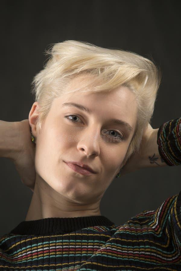 Allvarlig head och skuldrastående av den unga blonda kvinnan arkivfoto