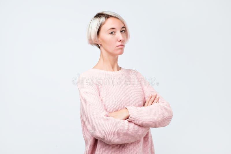 Allvarlig hipsterflicka i den rosa tröjan som poserar med korsade händer royaltyfria foton