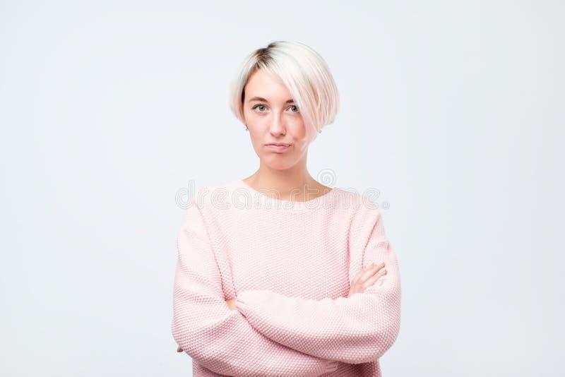 Allvarlig hipsterflicka i den rosa tröjan som poserar med korsade händer royaltyfria bilder
