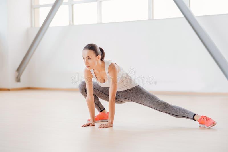 Allvarlig ihärdig kvinna som gör en fysisk övning royaltyfri foto