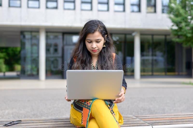 Allvarlig indisk flicka med bärbara datorn arkivbild