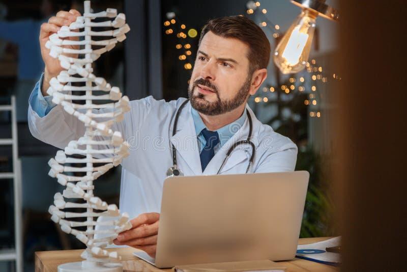 Allvarlig intelligent forskare som studerar genetik royaltyfri bild