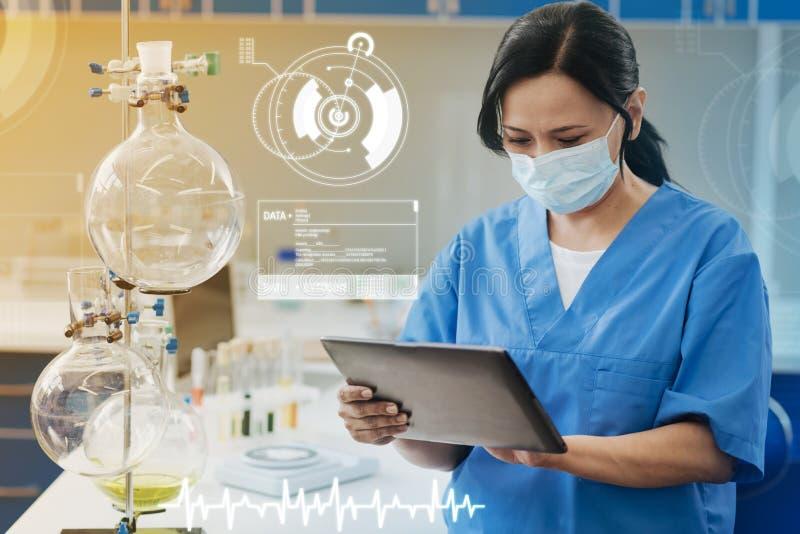Allvarlig kemist som ser skärmen av hennes minnestavla, medan vara i labbet royaltyfria bilder