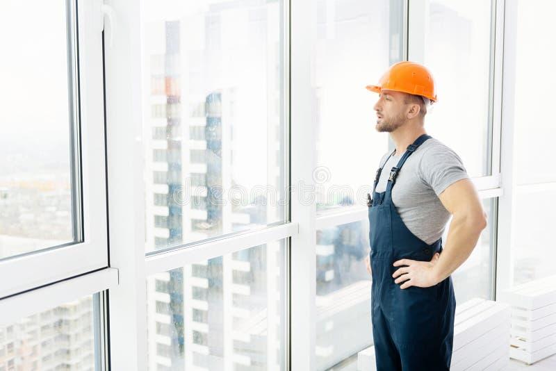 Allvarlig konstruktionstekniker som står det near fönstret royaltyfria foton