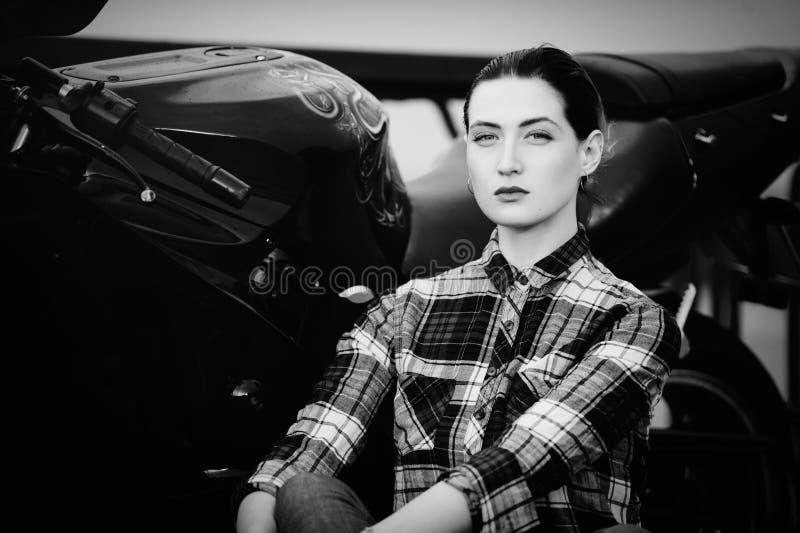 Allvarlig kvinna i en skjorta på en motorcykelbakgrund, slätat hår som är svartvitt fotografering för bildbyråer