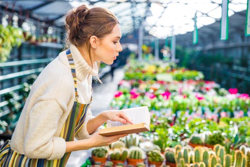 Allvarlig kvinna med boken som arbetar i trädgårds- mitt royaltyfria bilder