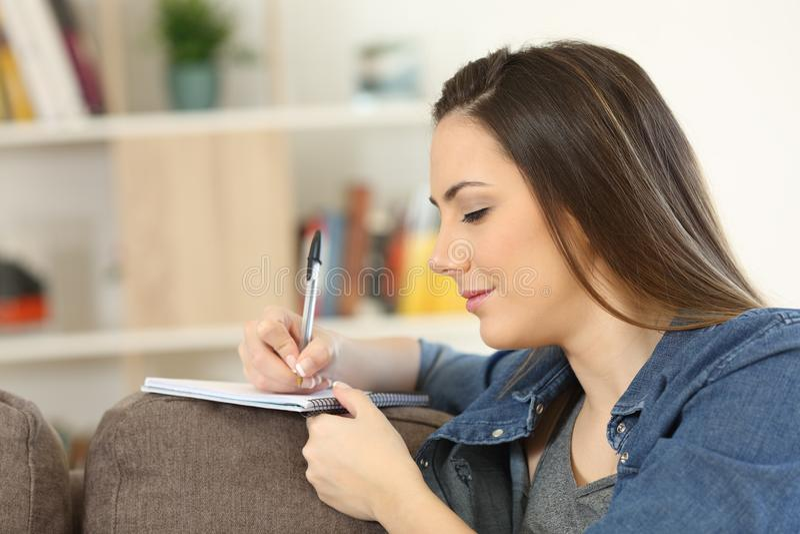 Allvarlig kvinnahandstil noterar hemma arkivbild