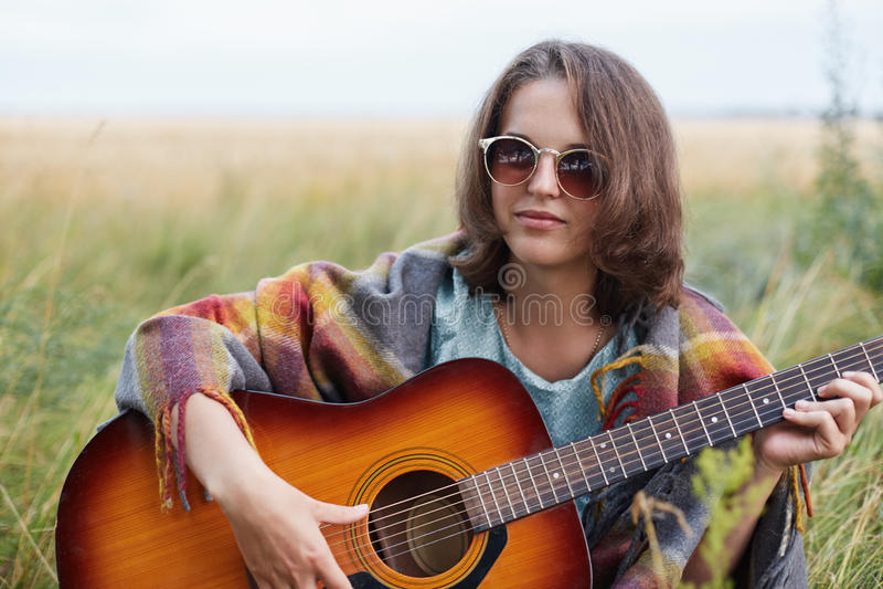 Allvarlig kvinnlig med bärande solglasögon för attraktivt utseende som sitter på ängen med den akustiska gitarren som försöker at arkivfoton
