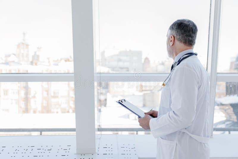 Allvarlig läkare som tänker om hans patient arkivfoto