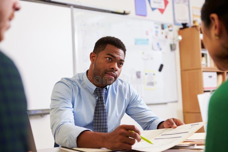 Allvarlig lärare på skrivbordet som talar till vuxenutbildningstudenter royaltyfria foton