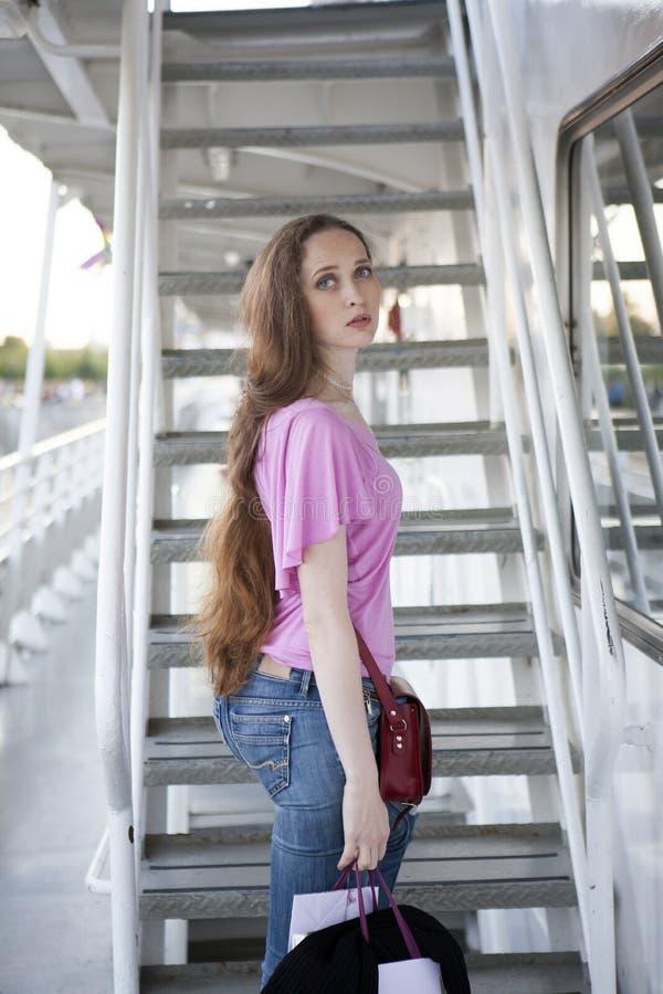 Allvarlig ledsen kvinna med långt hår och blåa ögon som bär en rosa färg T royaltyfria foton
