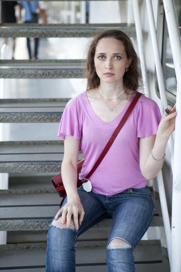 Allvarlig ledsen kvinna med långt hår och blåa ögon som bär en rosa färg T royaltyfri bild