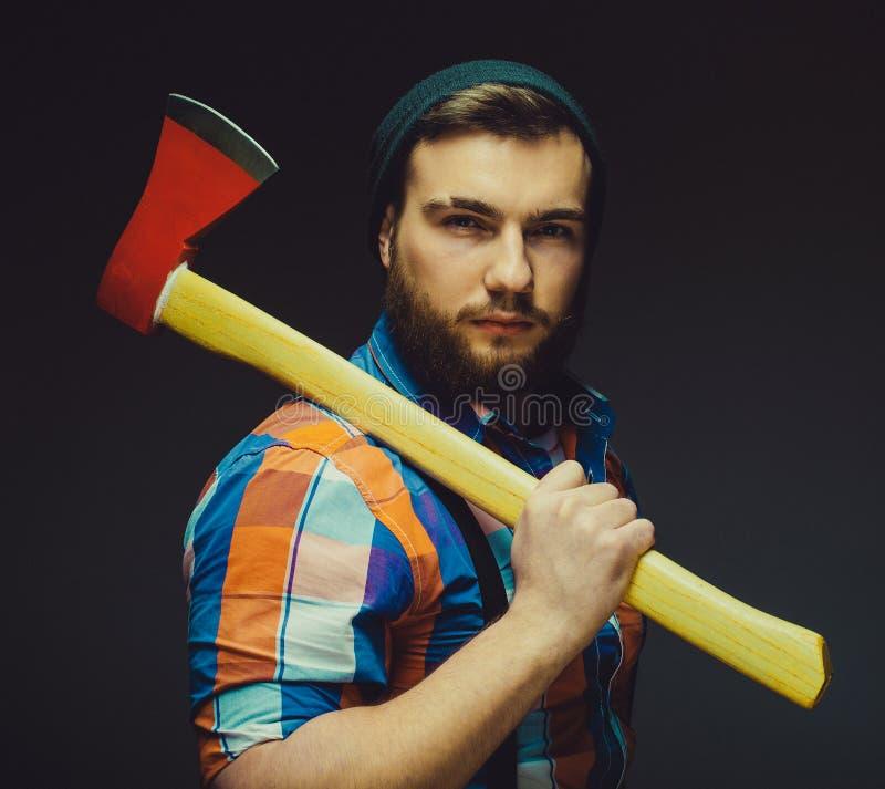 allvarlig lumberjack Säker ung skäggig man som rymmer en stor yxa royaltyfri foto