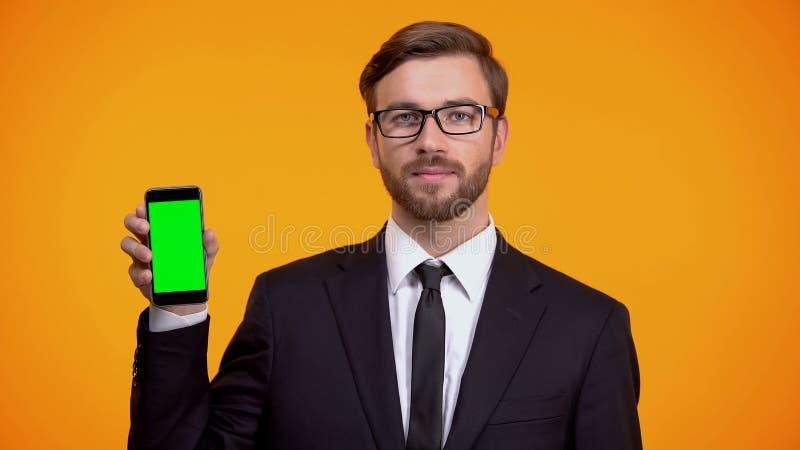 Allvarlig man i dr?kten som rymmer den gr?na sk?rmsmartphonen, online-schemaapp royaltyfria bilder
