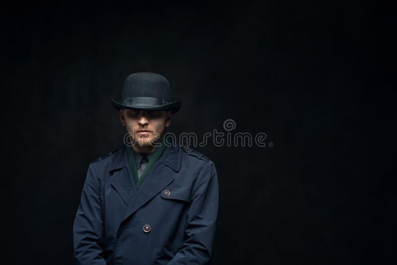Allvarlig man med en kall blick i en hatt på en mörk bakgrund royaltyfri bild