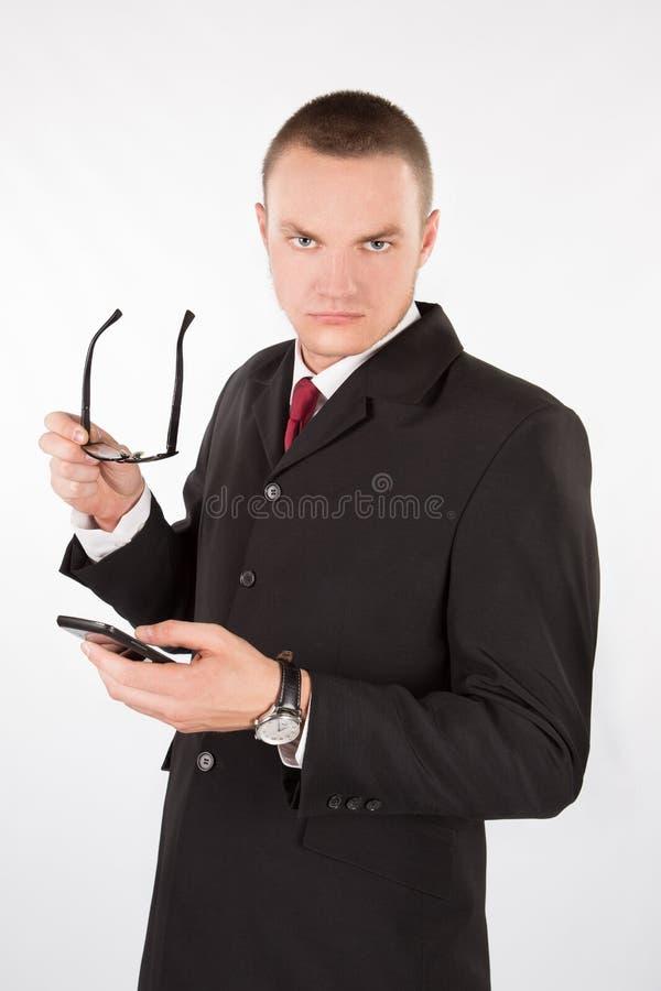 Allvarlig man med exponeringsglas och en telefon arkivfoto