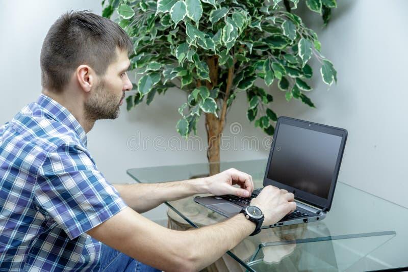 Allvarlig man som hemma arbetar på en bärbar dator royaltyfri foto