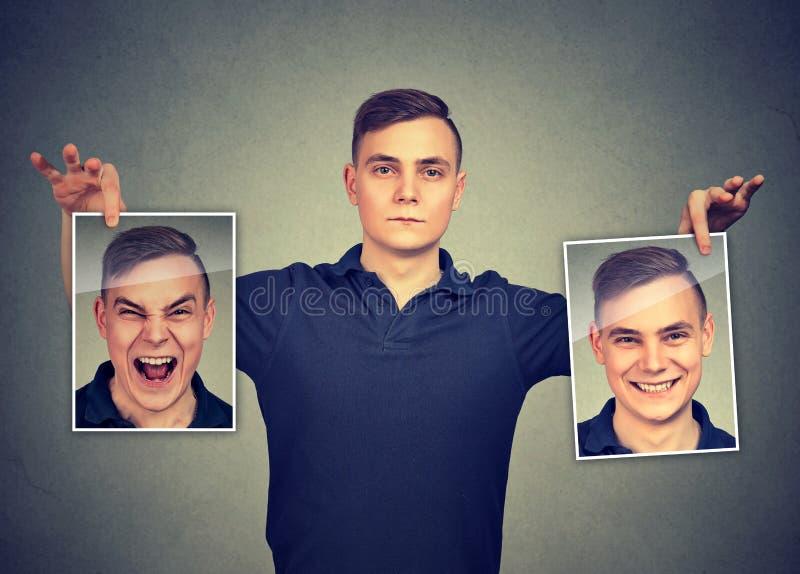 Allvarlig man som rymmer två olika framsidasinnesrörelsemaskeringar av honom fotografering för bildbyråer