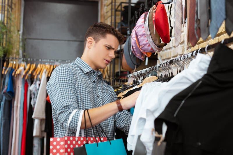 Allvarlig man som rynkar pannan, medan välja kläder i shoppa arkivbilder