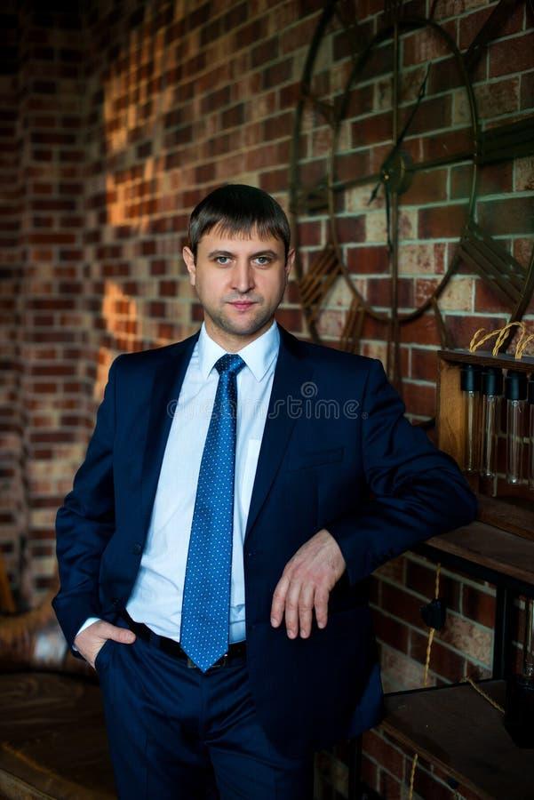 Allvarlig manlig advokataffärsman i strikt affärsdräkt och bandanseende i inre mot den bruna bakgrunden för tegelstenvägg fotografering för bildbyråer