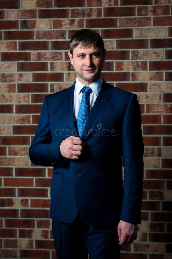 Allvarlig manlig advokataffärsman i strikt affärsdräkt och bandanseende i inre mot den bruna bakgrunden för tegelstenvägg royaltyfri bild