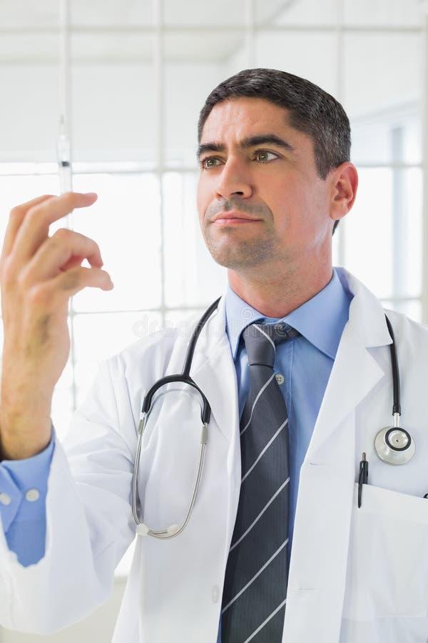 Allvarlig manlig doktor som rymmer en injektion royaltyfri fotografi