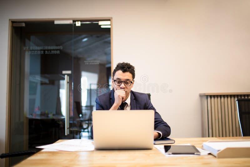 Allvarlig manlig ekonom som söker information på anteckningsboken arkivfoton
