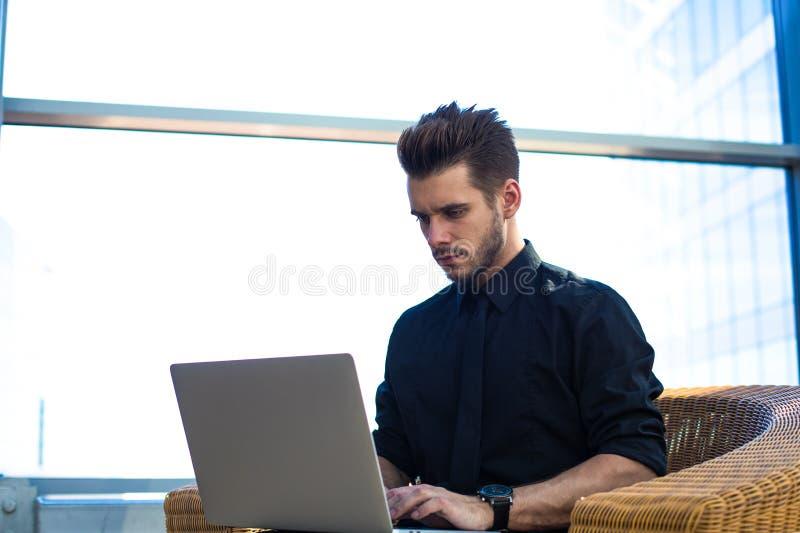 Allvarlig manlig entreprenör som arbetar på webbsidan via anteckningsboken Framstickandeonline-bokning arkivfoto
